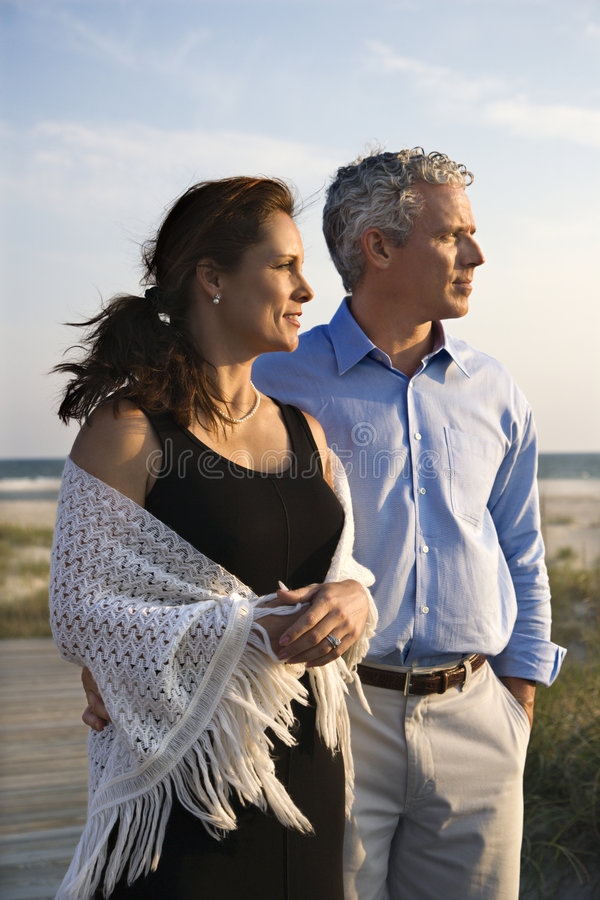 Couple at beach. Caucasian mid-adult couple looking off to side at beach stock images