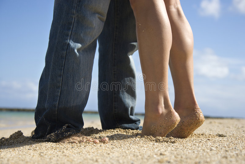 Couple on beach. Feet and legs of mid-adult Caucasian couple standing together on beach stock photography