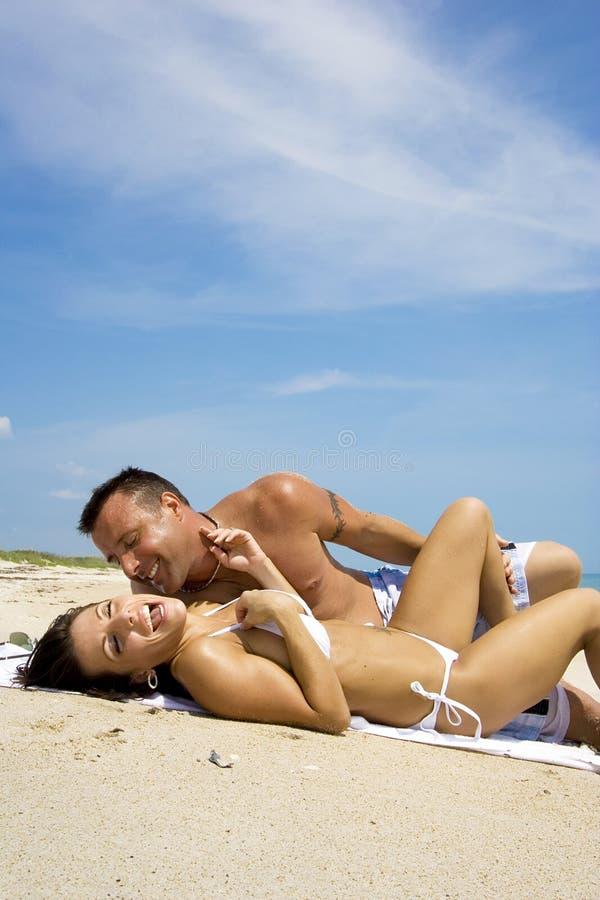 Couple on a beach. Couple enjoying the beach, sun and sand. Blue sky in the background stock photography