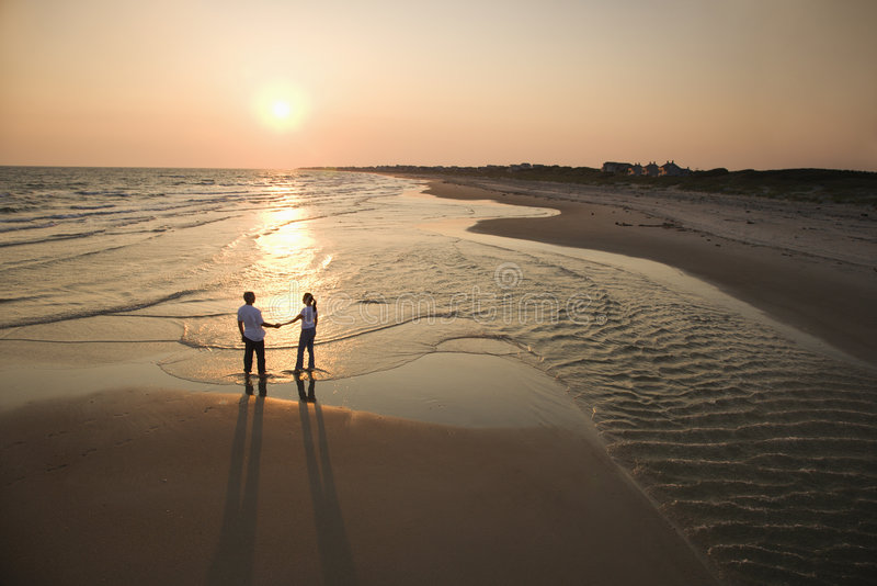 Couple on beach. Aerial view of romantic couple standing on beach holding hands on Bald Head Island, North Carolina
