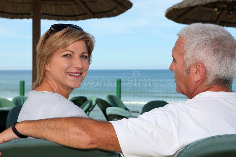 Couple at a beach cafe. Senior couple at a beach cafe stock photography