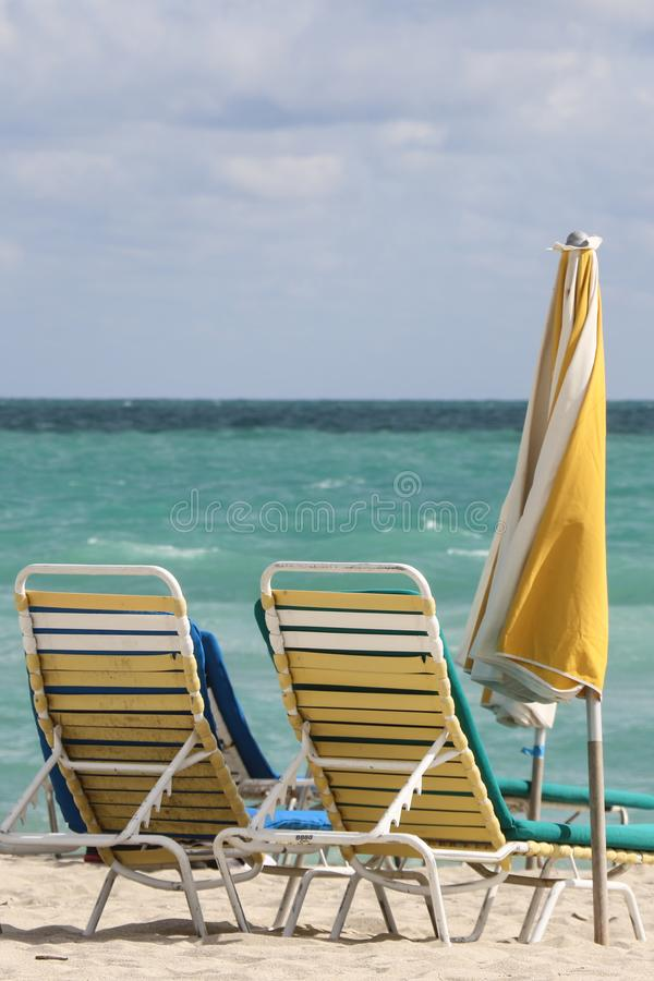 A couple of beach chairs and yellow umbrela in Miami beach stock photo