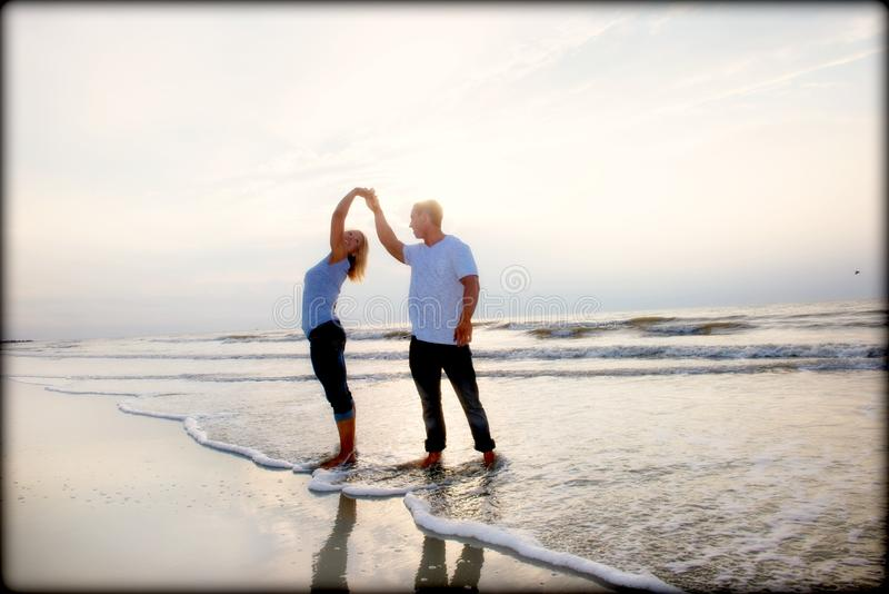 Couple on a beach. Loving couple enjoying the time spent together on the beach, standing bare foot in the water royalty free stock photography