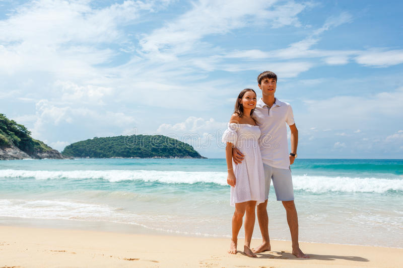 Couple on beach standing and looking far away royalty free stock photography