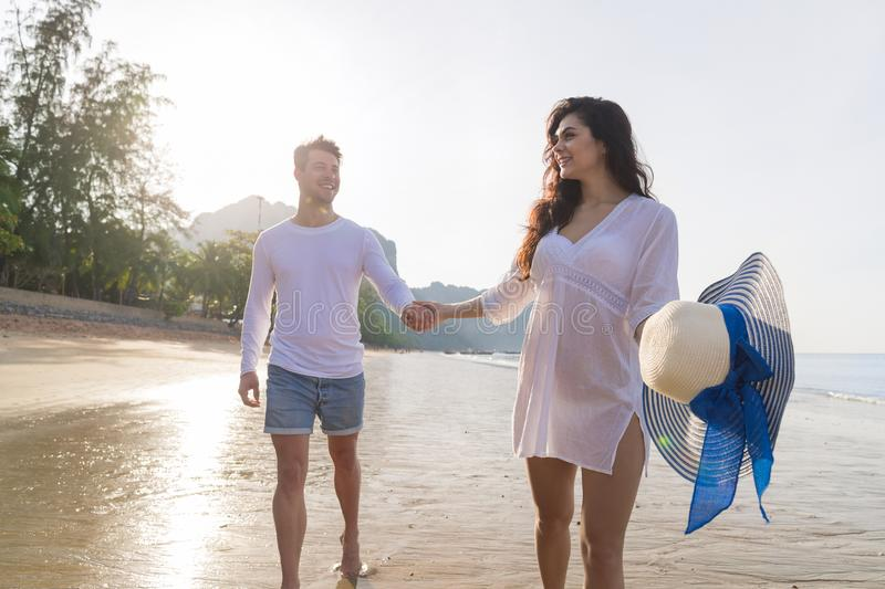 Couple On Beach Summer Vacation, Beautiful Young Happy People In Love Walking, Man Woman Smile Holding Hands. Sea Ocean Holiday Travel stock photography