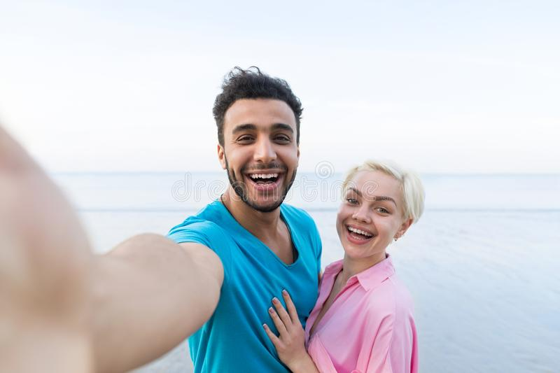 Couple On Beach Summer Vacation, Beautiful Young Happy People Taking Selfie Photo, Man Woman Embrace Sea. Ocean Holiday Travel stock image