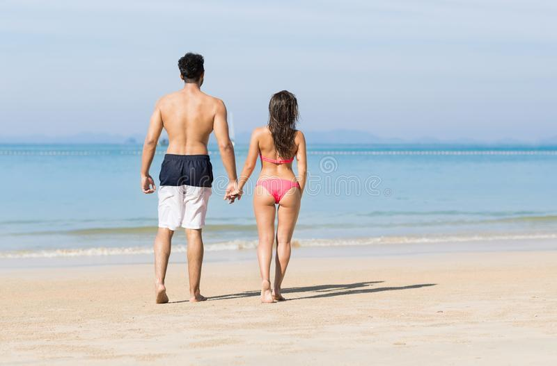 Couple On Beach Summer Vacation, Young People In Love Walking, Man Woman Holding Hands Sea Ocean. Holiday Travel stock photo