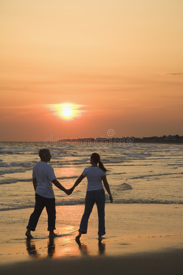 Couple on beach at sunsest. Mid-adult couple holding hands and walking on beach at sunset stock photography