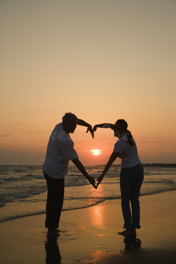 Couple on beach at sunset. Mid-adult couple making heart shape with arms on beach at sunset stock photo