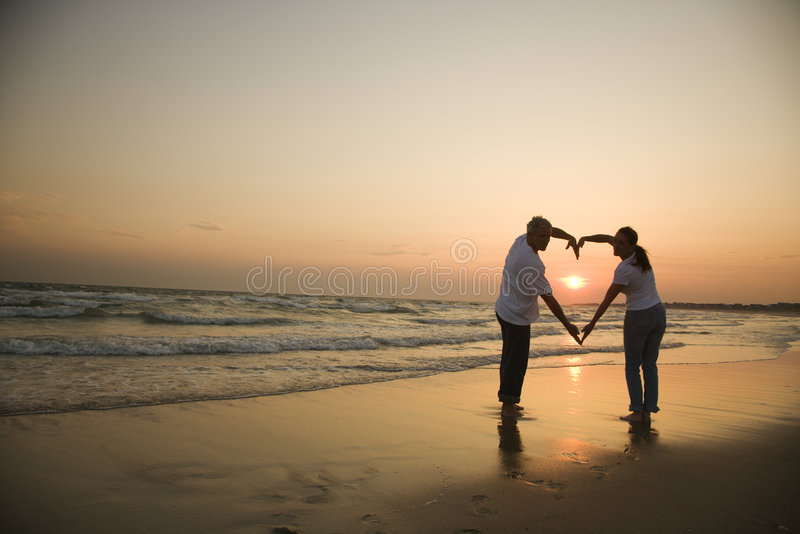Couple on beach at sunset. Mid-adult couple making heart shape with arms on beach at sunset stock image