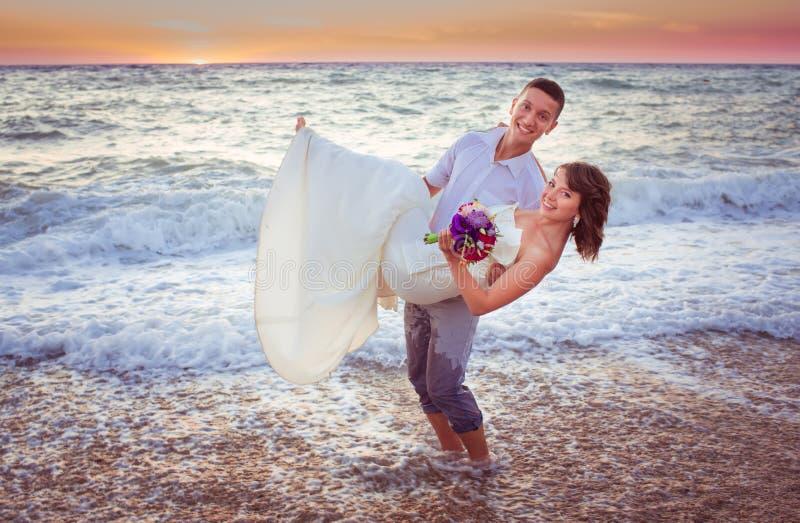 Couple on the beach. Wedding couple on the beach at sunset royalty free stock photos