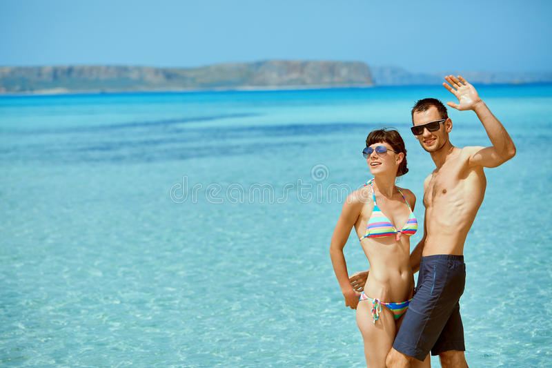 Couple on the beach. Young happy couple in love walking on the beach at the sunny day. Balos beach, Crete, Greece. newlyweds in a honeymoon on the sea and royalty free stock images
