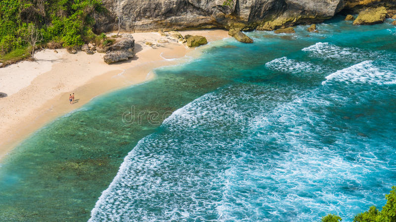 Couple on beautiful Atuh Beach with White Long Waves, Nusa Penida, Bali, Indonesia.  royalty free stock photo