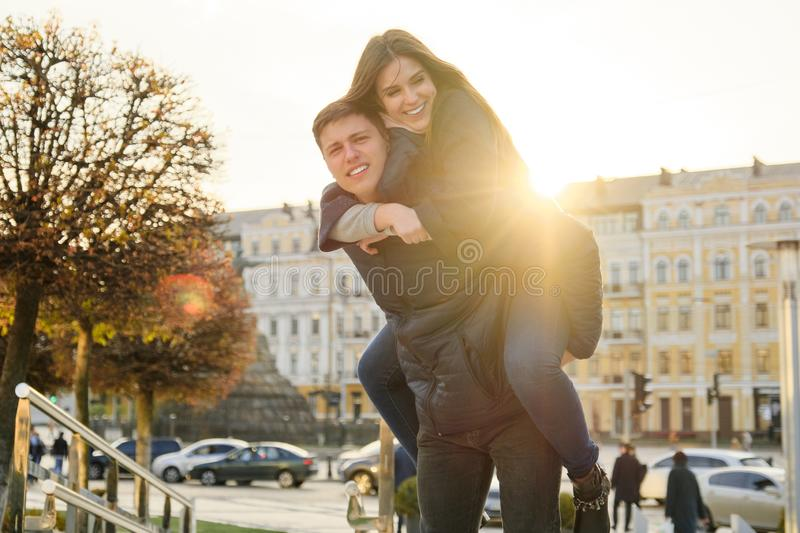 Couple of beautiful students are having fun in city, background spring city, young man and woman laughing, golden hour. Couple of beautiful students are having stock photo