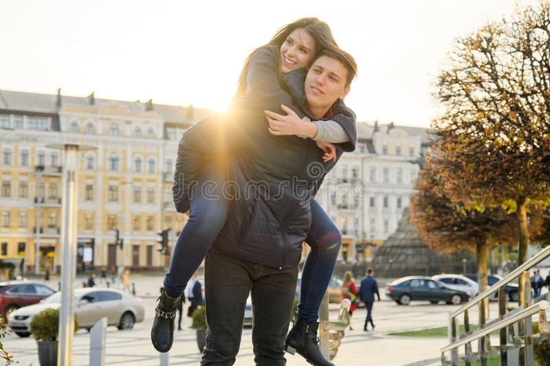 Couple of beautiful students are having fun in city, background spring city, young man and woman laughing, golden hour. Couple of beautiful students are having royalty free stock images