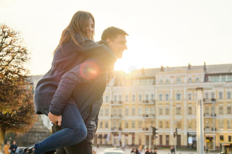 Couple of beautiful students are having fun in city, background spring city, young man and woman laughing, golden hour. Couple of beautiful students are having royalty free stock image