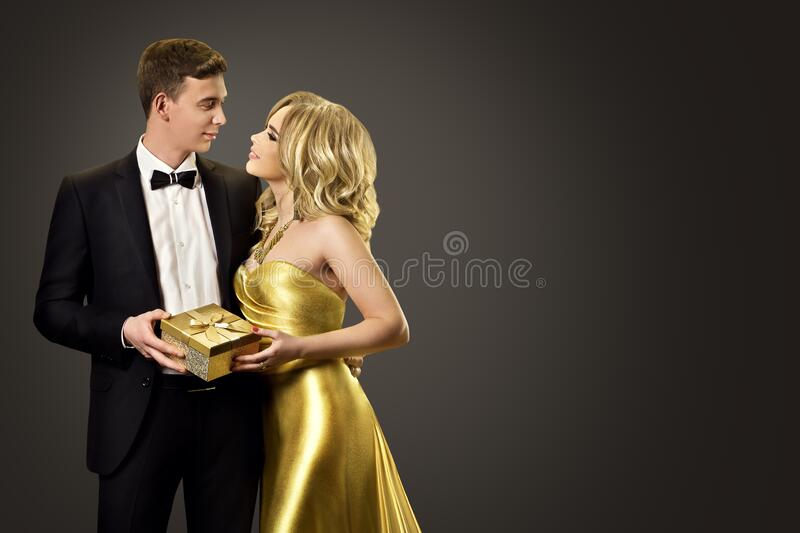 Couple Beauty Portrait with Present Gift, Beautiful Woman in Gold Dress and Elegant Man. Couple with Present Gift, Beautiful Woman in Gold Dress and Elegant Man royalty free stock photography