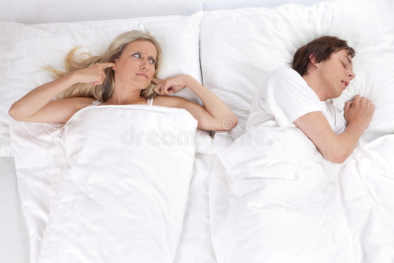 Couple in bed. With woman trying to sleep with man snoring