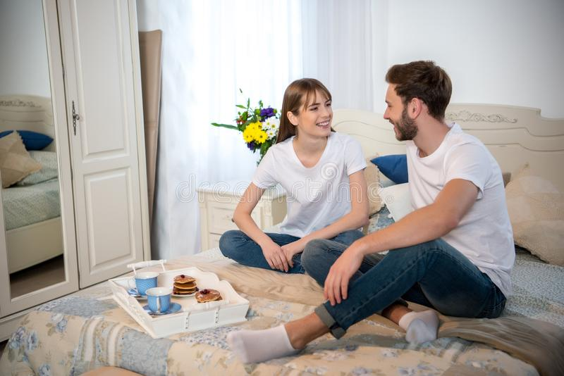 Couple on bed with breakfast on tray stock photography
