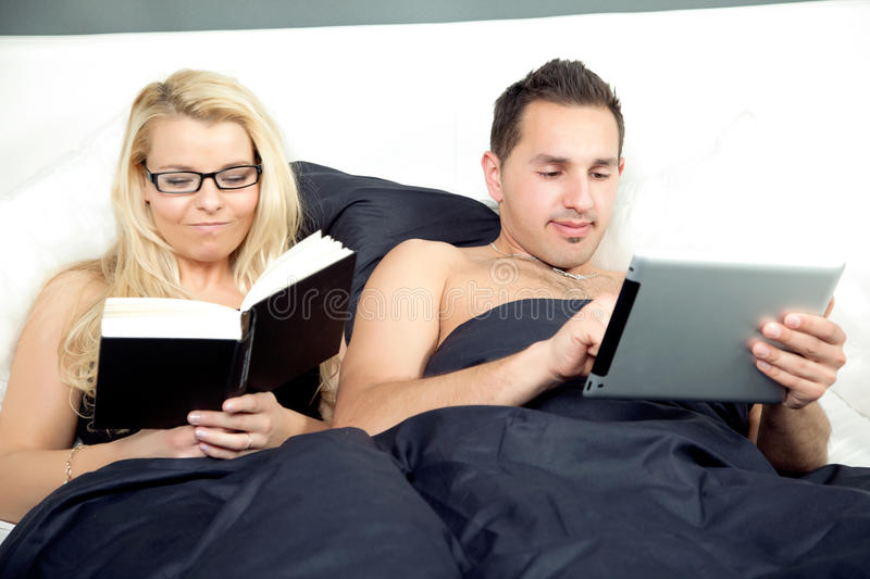 Couple in bed enjoying their individual oursuits. With the men surfing on his tablet computer while his wife, who is wearing glasses, reads a book royalty free stock images