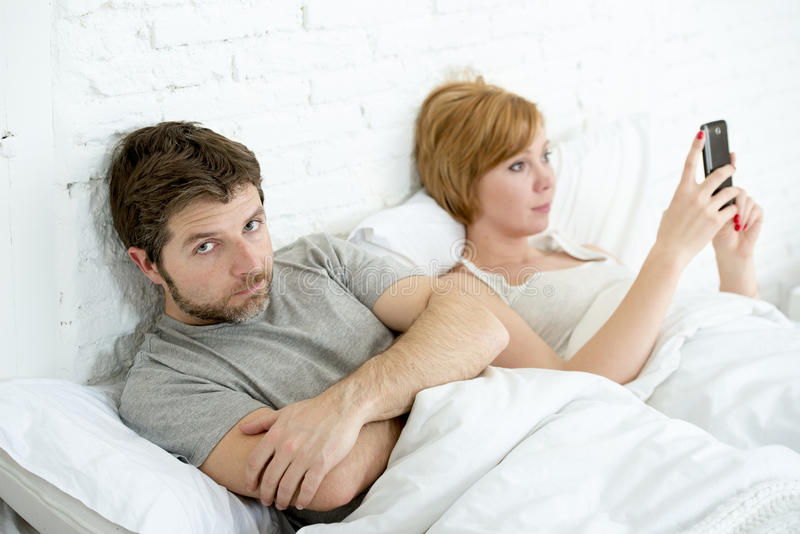Couple in bed husband frustrated upset and unsatisfied while his internet couple in bed husband frustrated upset unsatisfied while royalty free stock photo