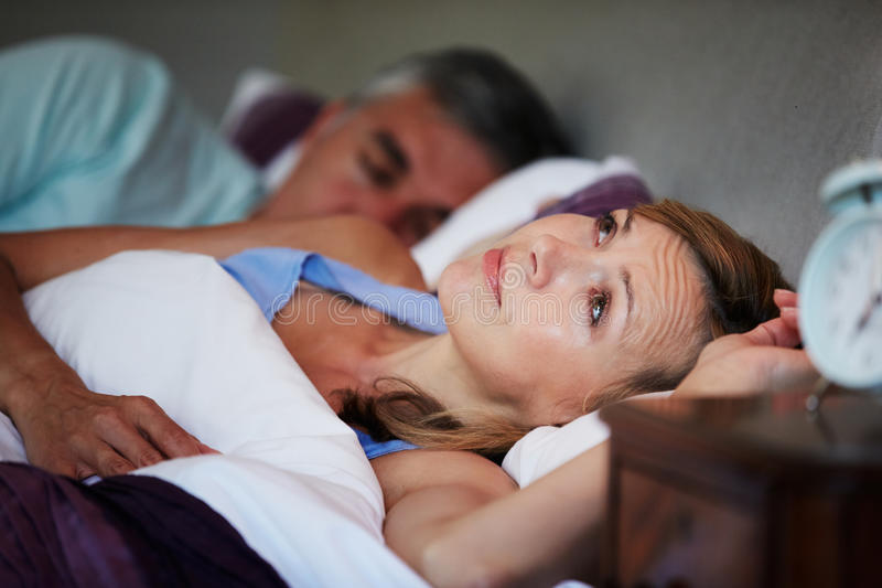 Couple In Bed With Wife Suffering From Insomnia. Lying Down Looking Up