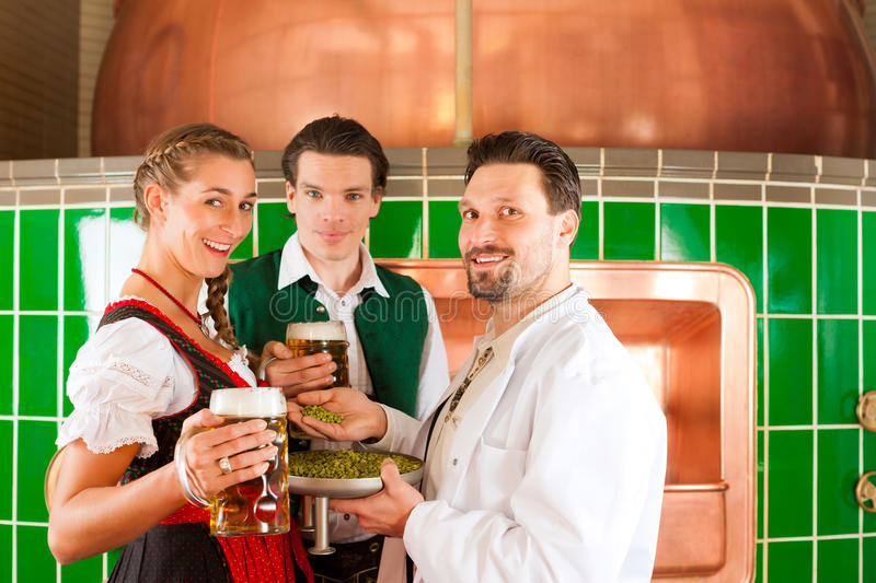 Couple with beer and their brewer in brewery. Man and women in Bavarian Tracht with male brewer, hops and beer stein in brewery stock photography