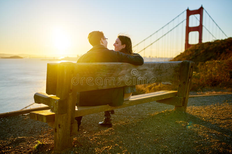 Couple on bench, Golden Gate Park, San Francisco. Couple sitting on bench along bay in Golden Gate Park with bridge in background in San Francisco, California at royalty free stock image