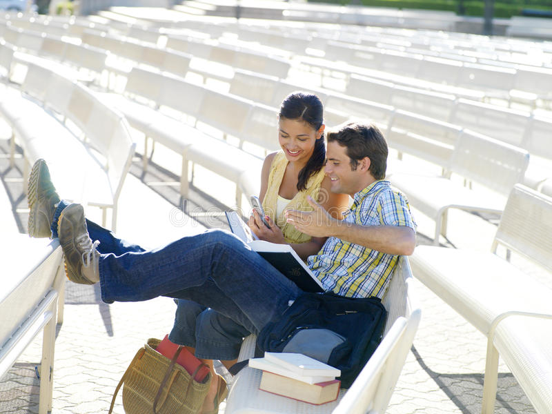 Couple on bench outdoors, woman with mobile phone, smiling. Couple on bench outdoors, women with mobile phone, smiling royalty free stock image