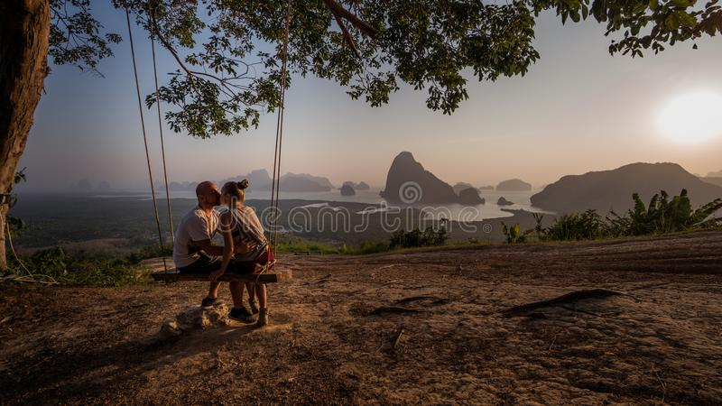 Couple on the bench over beautiful tropical mountain landscape. Kissing couple sitting on the swinging bench over beautiful tropical mountain landscape during stock image