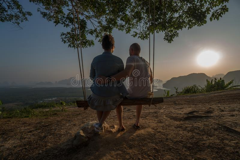 Couple on the bench over beautiful tropical mountain landscape. Couple sitting on the swinging bench over beautiful tropical mountain landscape during sunrise royalty free stock photo