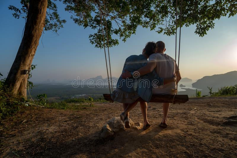 Couple on the bench over beautiful tropical mountain landscape. Couple sitting on the swinging bench over beautiful tropical mountain landscape during sunrise royalty free stock photography