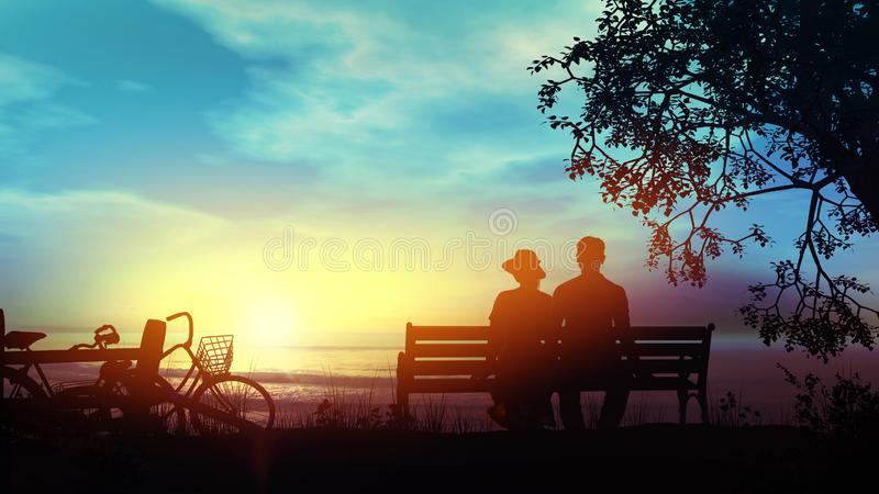 Couple on a bench watching the ocean after a bike ride. Silhouettes of a couple sitting on a bench and looking at the setting sun over the ocean royalty free stock photos