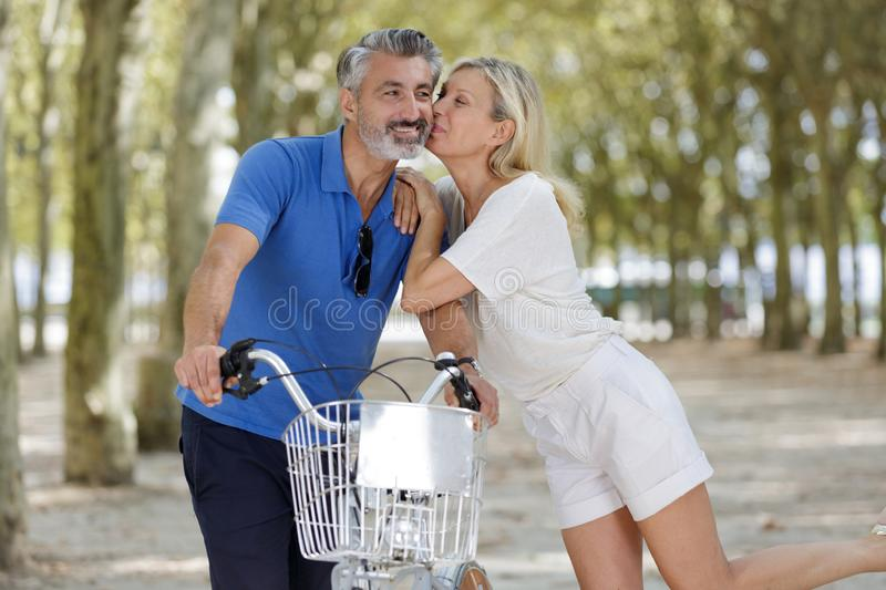 Couple with bicycles standing during kissing royalty free stock photo