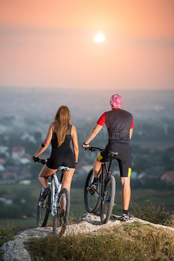 Couple bicyclist with mountain bikes on the hill at sunset stock photos