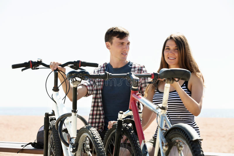 Couple with bikes on beach stock photo