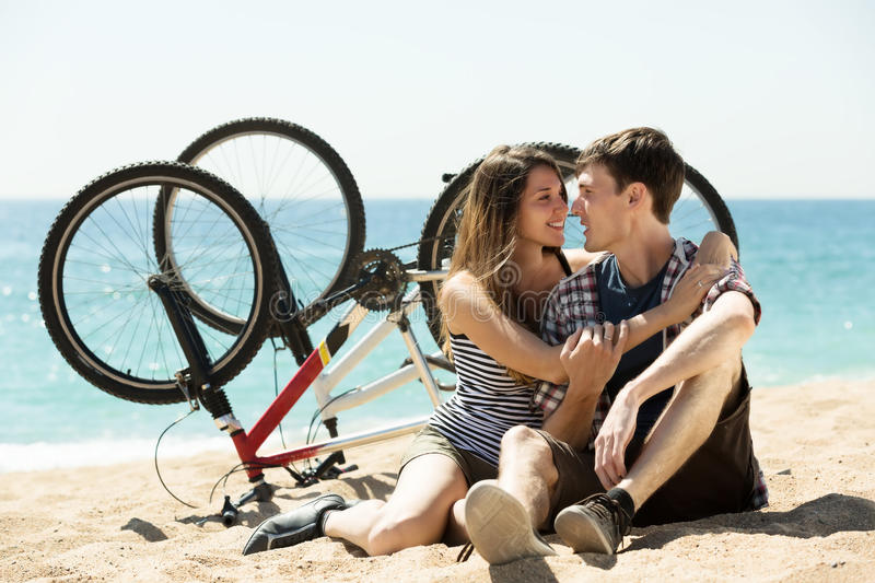 Couple with bikes on beach. Lovely young couple with bikes resting on beach at sunny day stock photography