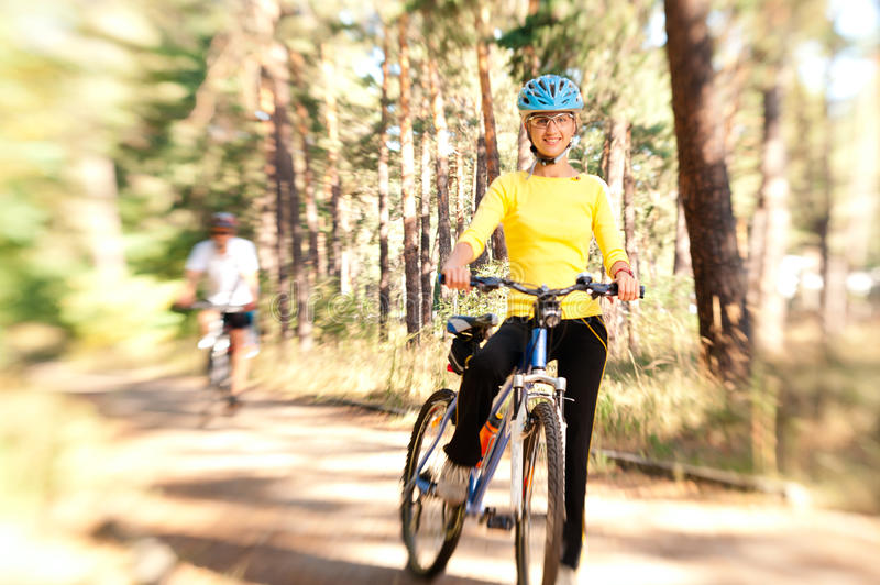 Couple on bikes in the sunny forest royalty free stock photo