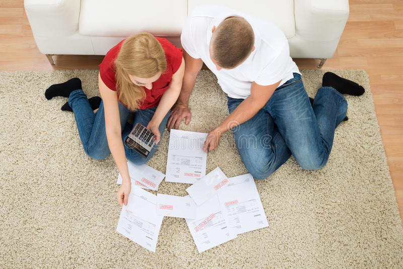 Couple with bills and calculator royalty free stock photo