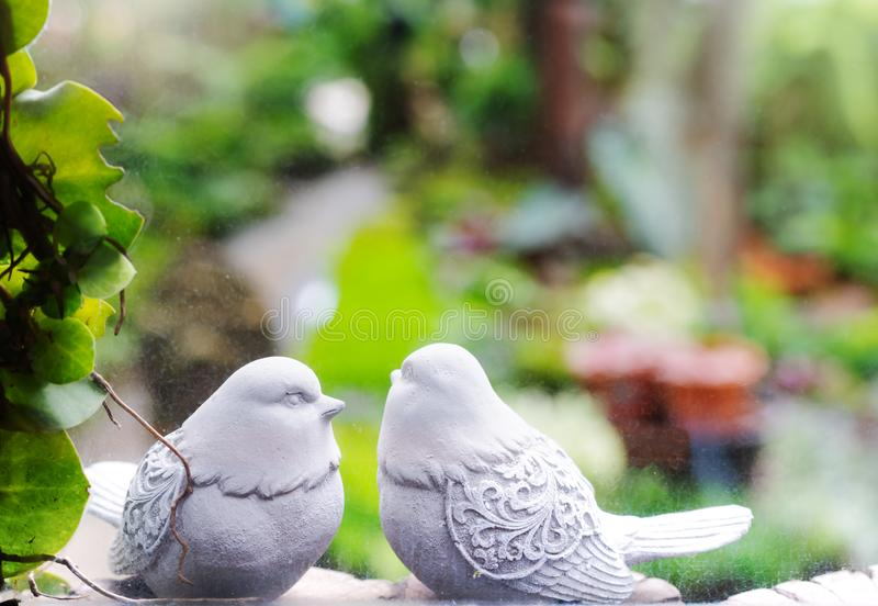 Couple birds, two white bird statues in garden through the window stock photography