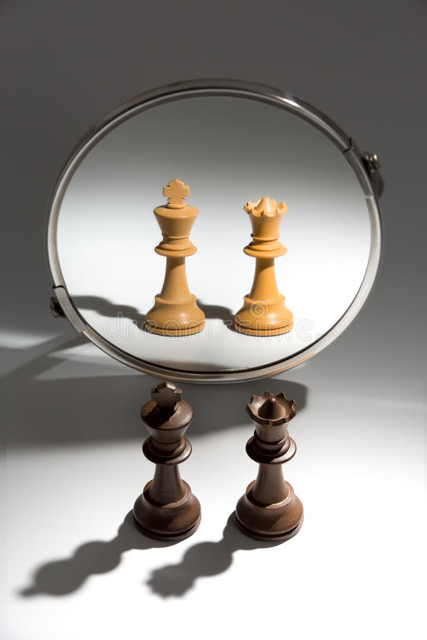 A couple of a black king and queen is looking in a mirror to see themselves as a white couple. stock photo
