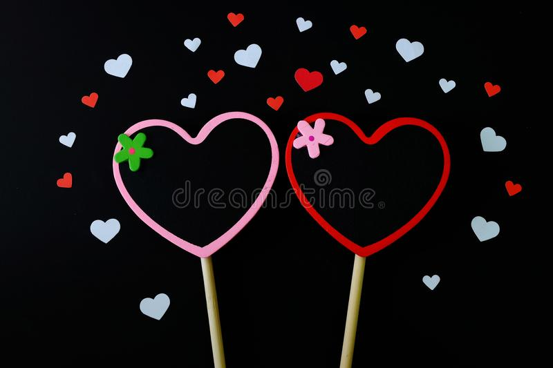 Couple of small heart shape blackboard surrounded by white and red paper heart on black background. royalty free stock photos