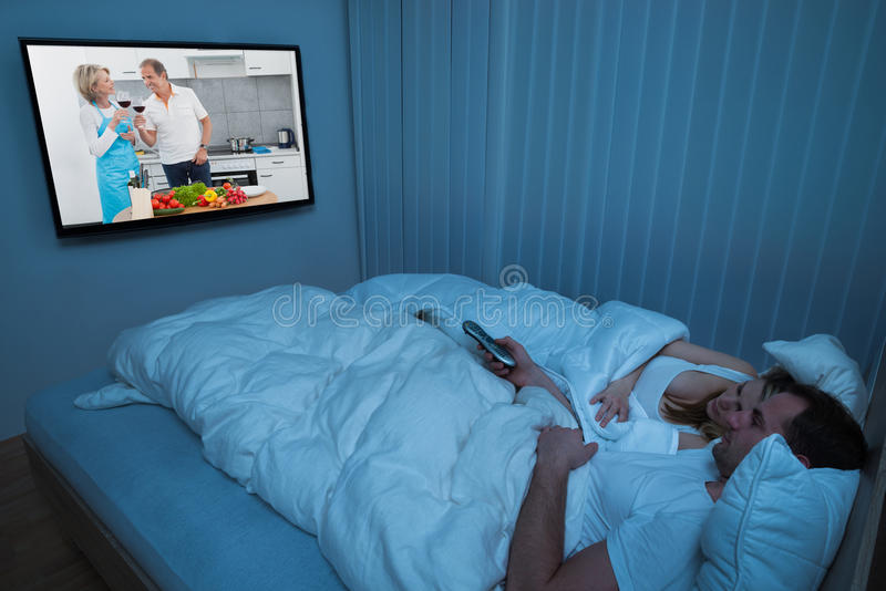 Couple with blanket watching television royalty free stock photography