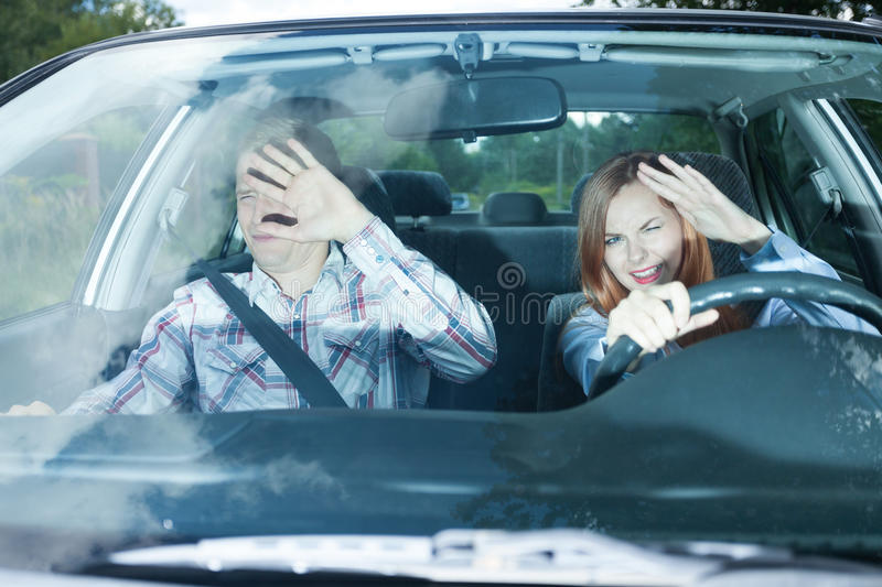 Couple blinded in a car. Young couple in car blinded by high beam lights royalty free stock images