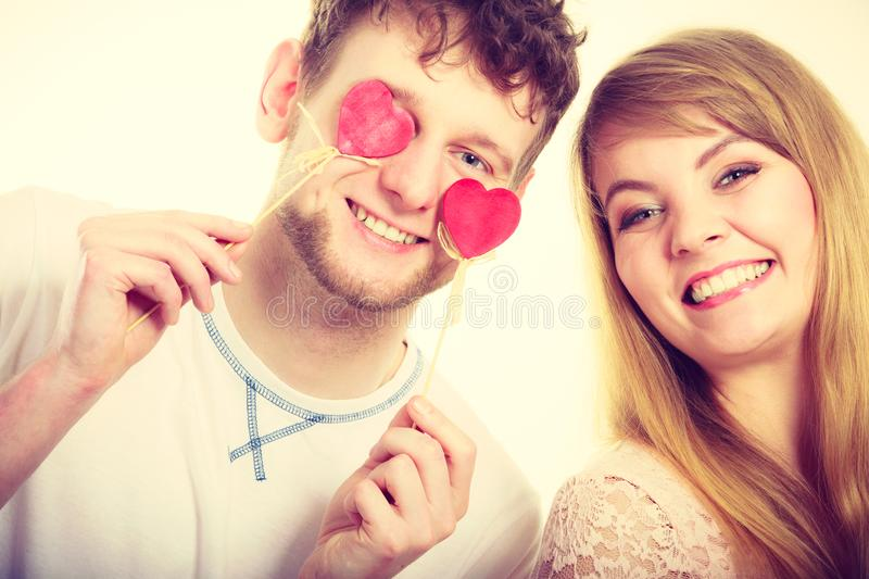 Couple blinded by their love. Love and happiness concept. Cheerful enjoyable young couple with little small hearts on sticks covering women men eyes. Lovers royalty free stock photos