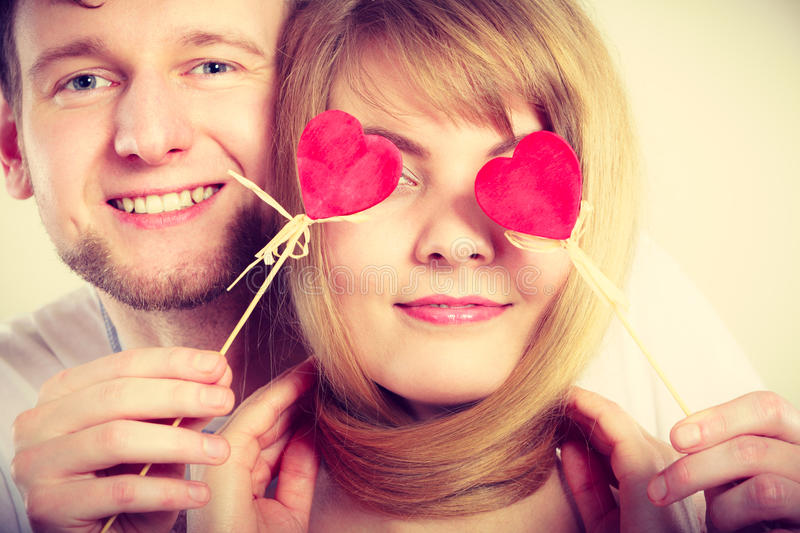 Couple blinded by their love. Love and happiness concept. Cheerful enjoyable young couple with little small hearts on sticks covering women men eyes. Lovers stock photo