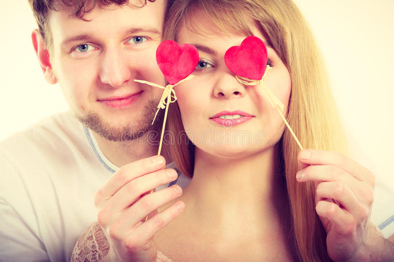Couple blinded by their love. Love and happiness concept. Cheerful enjoyable young couple with little small hearts on sticks covering women men eyes. Lovers royalty free stock image