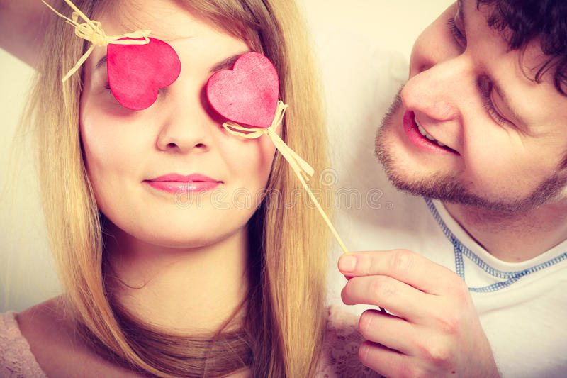 Couple blinded by their love. Love and happiness concept. Cheerful enjoyable young couple with little small hearts on sticks covering women men eyes. Lovers stock images