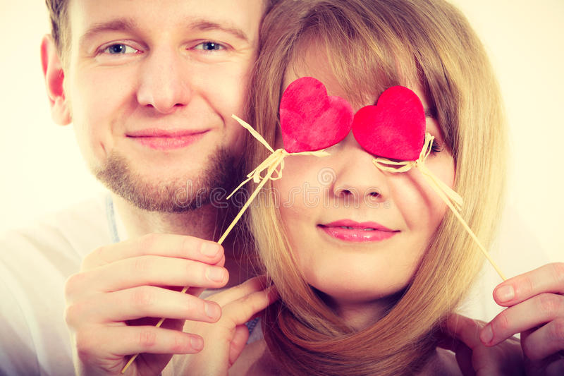 Couple blinded by their love. Love and happiness concept. Cheerful enjoyable young couple with little small hearts on sticks covering women men eyes. Lovers stock photos