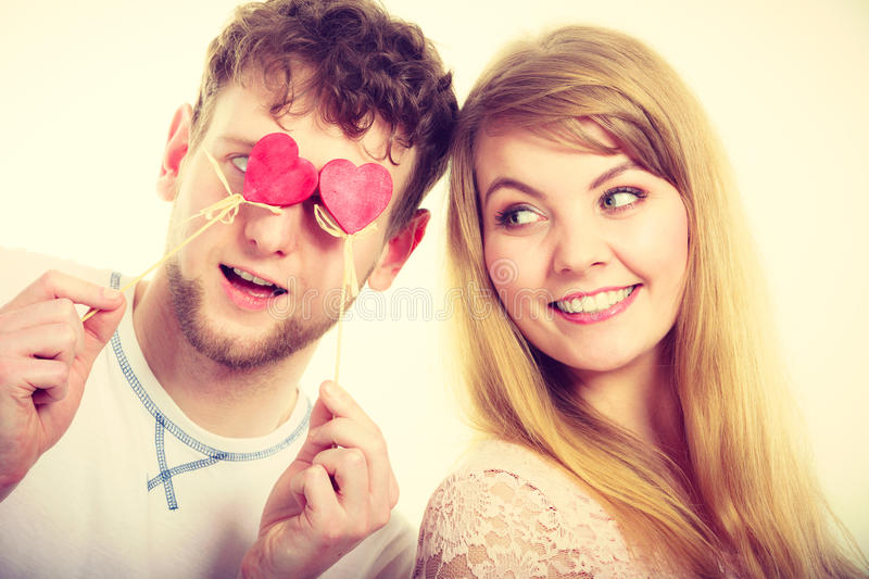 Couple blinded by their love. Love and happiness concept. Cheerful enjoyable young couple with little small hearts on sticks covering women men eyes. Lovers stock image